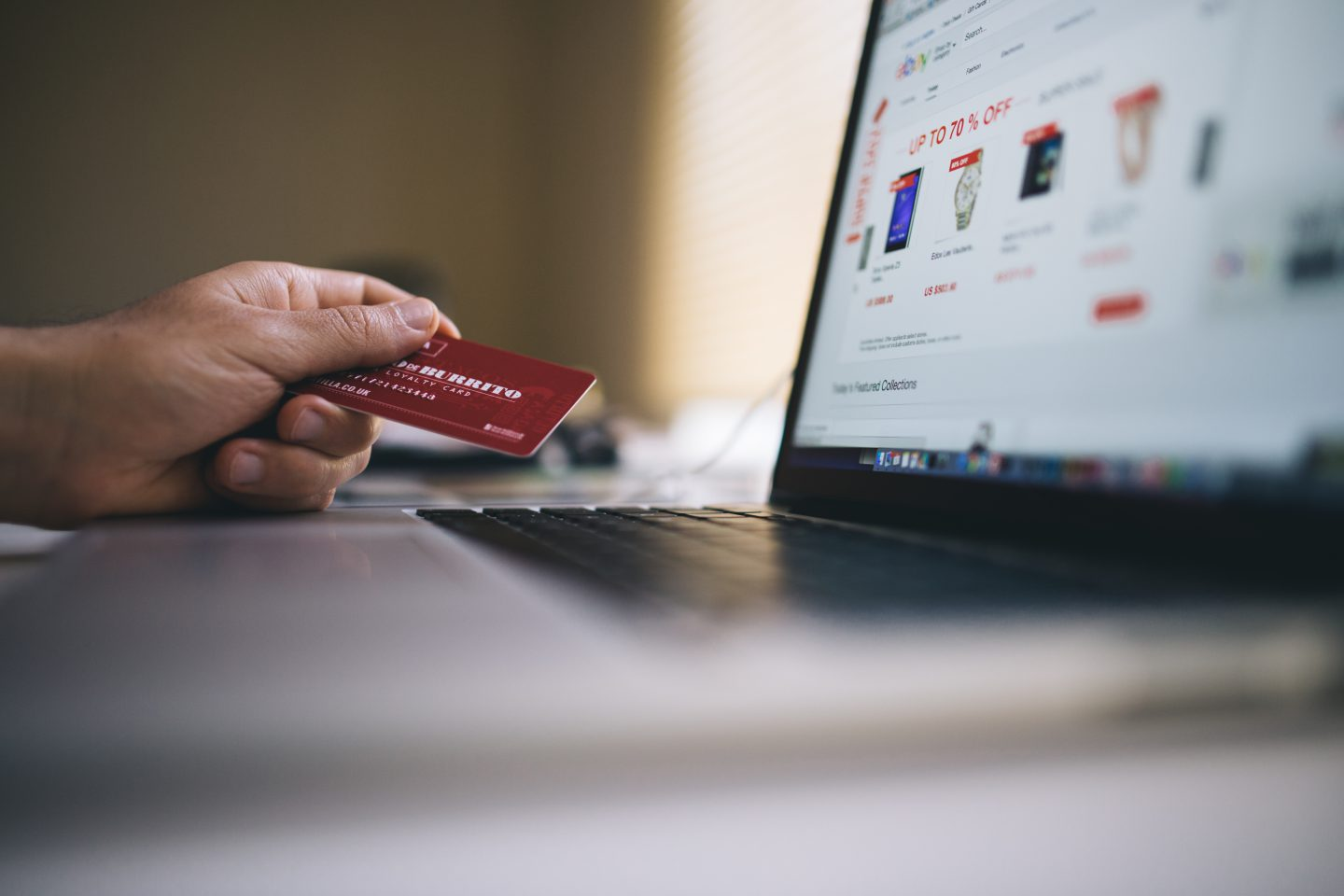 laptop with person holding credit card